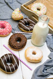 Bottle of milk and colorful donuts with chocolate Stock Photos