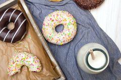 Bottle of milk and colorful donuts with chocolate and icing,. Selective focus Royalty Free Stock Photos
