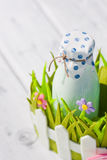 Bottle of milk in decorative basket with flowers Royalty Free Stock Images