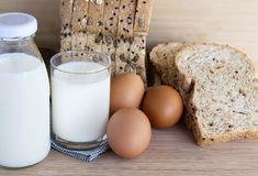 Bottle of milk, eggs, and bread on the wooden table. With copy space for text Stock Image