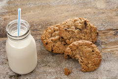 Bottle of milk with half eaten cookies Stock Photos