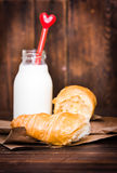 Bottle of milk with heart and croissant on wood Stock Images