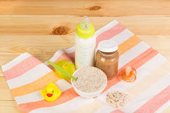 Bottle of milk, oatmeal, mashed potatoes, nipple on light wood. royalty free stock images