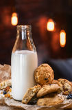 Bottle of milk with raisin cookies. Against bokeh evening lights Stock Photography
