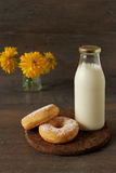 Bottle of milk and simple donuts on rustic table Royalty Free Stock Image