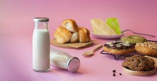 Bottle of milk and various bakeries on a pink background. Glass bottle of milk and various bakeries on a pink background, bakery, beverage, breakfast, calcium royalty free stock photo