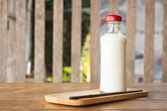 Bottle of milk on wooden table Stock Photos