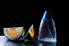 Bottle of modern male perfume and citrus slices. On dark background Stock Images
