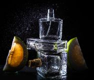 Bottle of modern male perfume and citrus slices. On dark background Stock Photo