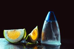 Bottle of modern male perfume and citrus slices. On dark background Royalty Free Stock Image