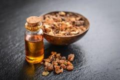 A bottle of myrrh essential oil. With myrrh resin on a black slate background Stock Photography