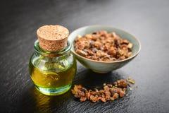 A bottle of myrrh essential oil. With myrrh resin on a black slate background Royalty Free Stock Photography