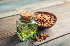 A bottle of myrrh essential oil. With myrrh resin on a wooden background Royalty Free Stock Photos