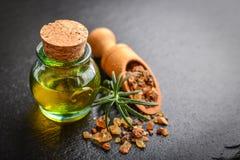 A bottle of myrrh essential oil. With myrrh resin on a black slate background Stock Images