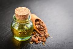 A bottle of myrrh essential oil. With myrrh resin on a black slate background Stock Image