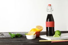 Bottle with natural charcoal lemonade. On table against light background royalty free stock image