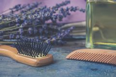 Bottle of natural cosmetic lavender oil, hair and body treatment, wooden massage brush and comb. Bottle of natural cosmetic lavender oil, hair and body treatment stock photography