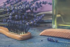 Bottle of natural cosmetic lavender oil, hair and body treatment, wooden massage brush and comb. Bottle of natural cosmetic lavender oil, hair and body treatment stock image