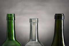 Bottle necks. Picture of wine bottle necks on a row, on a grey and black background royalty free stock photo