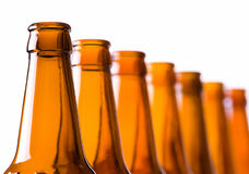 Bottle necks in a row. Closeup of empty beer bottles, selective depth of focus on first Royalty Free Stock Photo
