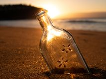 A bottle buried in the sand. A bottle with no cap in the sand on a beach, with the sun shining in the background Royalty Free Stock Photos