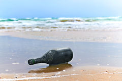 Bottle with a note on the sea shore Royalty Free Stock Photography