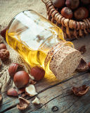 Bottle of nut oil and basket with filberts on table Royalty Free Stock Photos