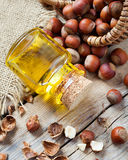 Bottle of nut oil and basket with hazelnuts on old kitchen table Royalty Free Stock Photos