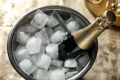 Free Bottle Of Champagne In Bucket With Cubes Ice On Table. Stock Images - 144787064