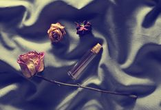 Bottle Of Perfume And Buds Of Dried Roses On A Gray Silk Backg Royalty Free Stock Photography