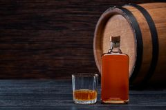 Free Bottle Of Whiskey On A Black Wooden In Oak Barrels Royalty Free Stock Photography - 111050687