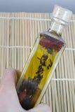 Bottle of Oil. Decorative olive oil bottle on straw mat Stock Photo
