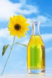 Bottle of oil against sunflowers in fblue sky stock images