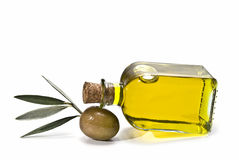 A bottle of oil lying on one olive. Stock Photos