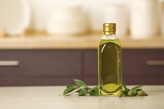 Bottle of oil and olive tree twig on table. Against blurred background. Space for text stock photography