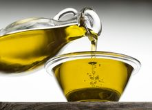 A bottle of Oil pouring in a glass Royalty Free Stock Images