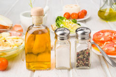 Bottle of oil salt and pepper shakers on the table Stock Photography