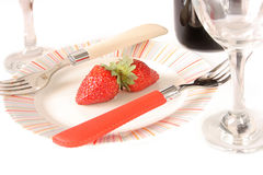 The bottle of old red wine. Old red wine bottle and strawberry on the plate Stock Images