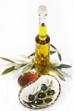 Bottle of olive oil. A bottle of olive oil with texture background and olive leafs Stock Image