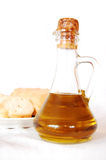 A bottle of olive oil. A glass bottle of olive oil and a plate with some fresh bread in the background Royalty Free Stock Image