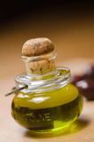 Bottle of Olive Oil. A small bottle of extra virgin olive oil with olives against a graduated brown background Royalty Free Stock Images
