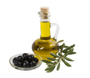 A bottle with olive oil, black olives on a plate and olive branch with leaves on a white background. Isolated Stock Image