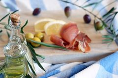Bottle with olive oil on a breakfast background with olives and bacon in the morning.  Royalty Free Stock Photos
