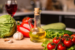 Bottle of olive oil with fresh salad vegetables Stock Photo