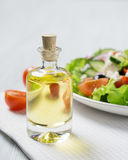 Bottle of olive oil with fresh vegetable Greek salad. Closeup Stock Photo