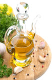 Bottle of olive oil, garlic, spices and fresh herbs on board Royalty Free Stock Image