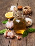 Bottle with olive oil. Olive oil with  green basil and  garlic on a table Stock Photo