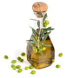 Bottle of olive oil and green olives. Glass bottle of olive oil with branch of olives   on white background Stock Photos