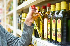 Bottle of olive oil in hand buyer at grocery. Bottle of olive oil in the hand of the buyer at the grocery store stock photo