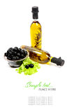 A bottle of olive oil with herbs and black olives. Isolated on a white background Royalty Free Stock Photo